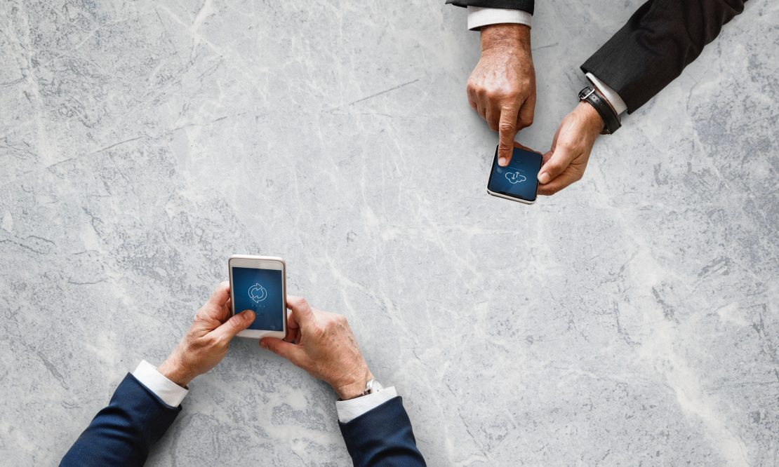 Two sets of hands working on mobile devices
