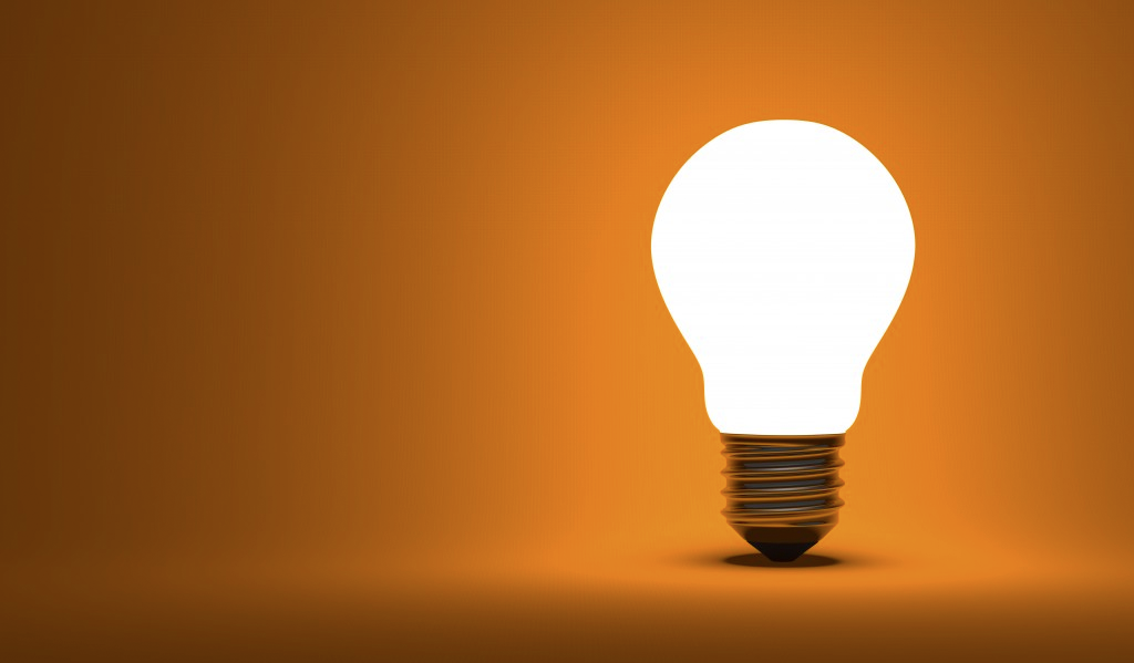 A lightbulb illuminated against an orange background.