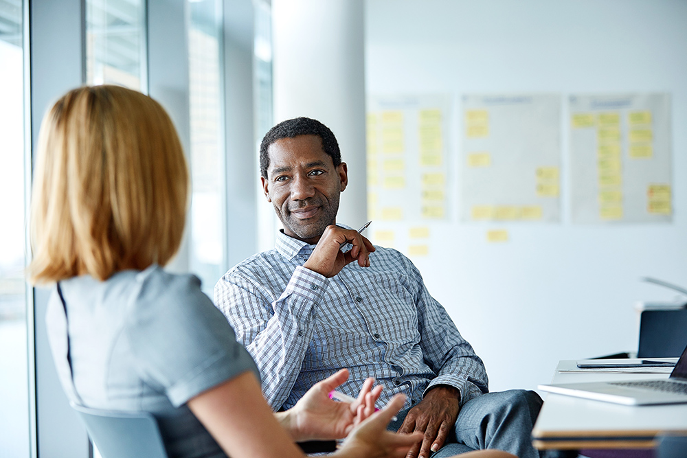 Two colleagues talking together while sitting in a modern office