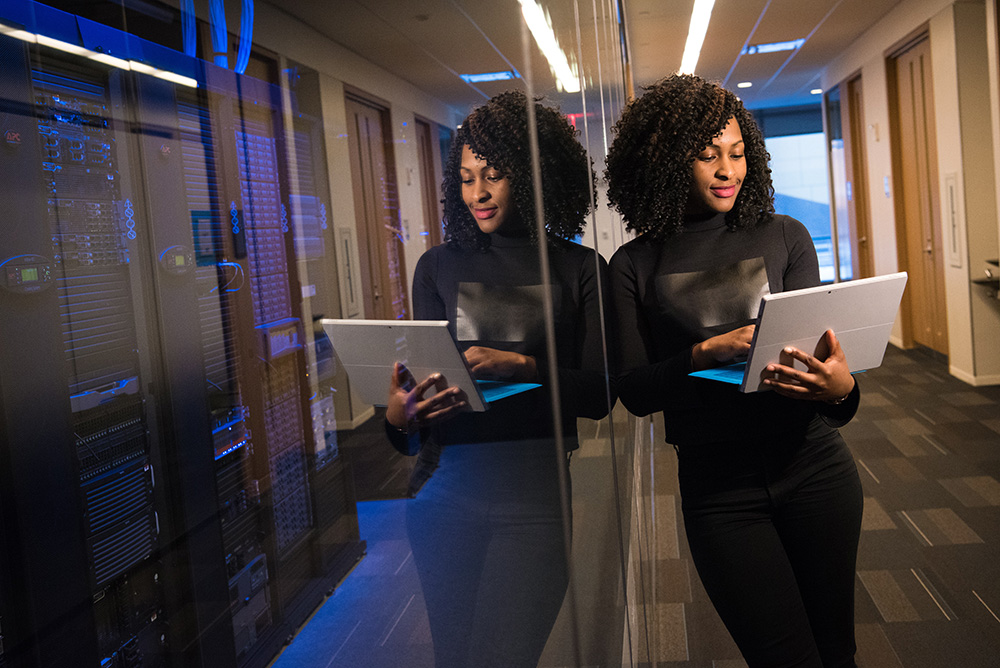 Women holding a laptop next to server room